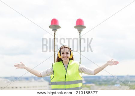 Attractive Cute Worker Woman In Green West And Earmuffs Stand On Roof, Hold Tablet