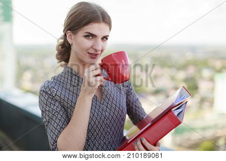 Attractive Businesslady In Patterned Dress Stand On The Roof And Hold Paper Folder And Red Cup