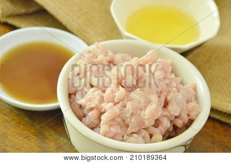 raw minced pork with soy sauce and oil on wooden table