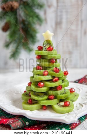 Healthy dessert idea for kids party - funny edible kiwi pomegranate Christmas tree, beautiful New Year background