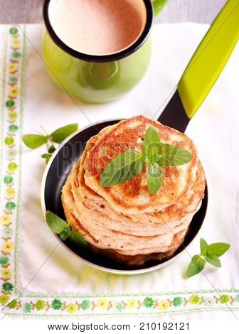 Pile of oat pancakes in a pan