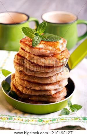 Pile of oat pancakes with syrup in a pan