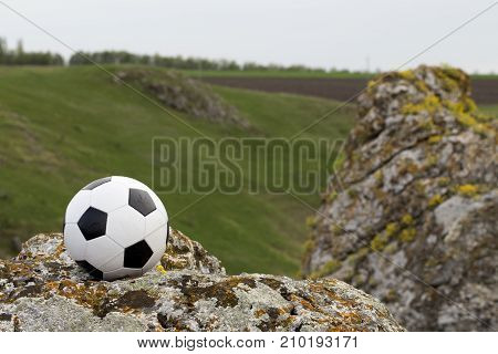 Football and the landscape. Ball is situated on the rock.