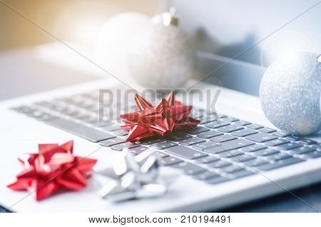 Christmas decoration on a computer. Red and silver ribbon on laptop desktop. Computer on a wooden table and white wall. Business concept during a holiday. Xmas concept.