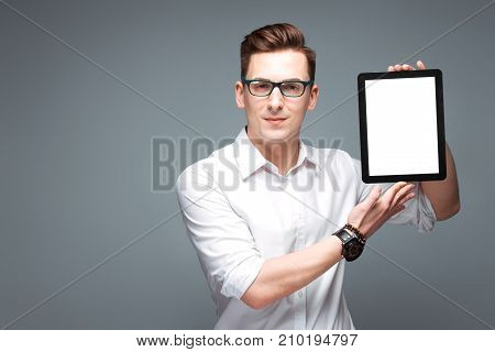 Attractive Young Businessman In Costly Watch, Black Glasses And White Shirt Hold Empty Tablet