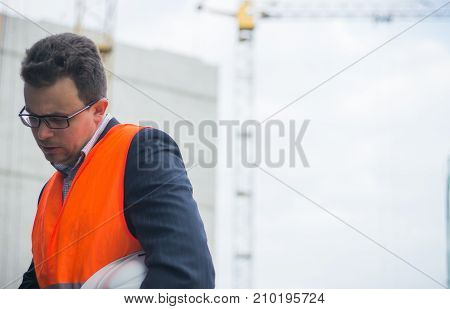 Worker Or Engineer Holding In Hands Helmet For Workers Security On Background Of New Highrise Apartm
