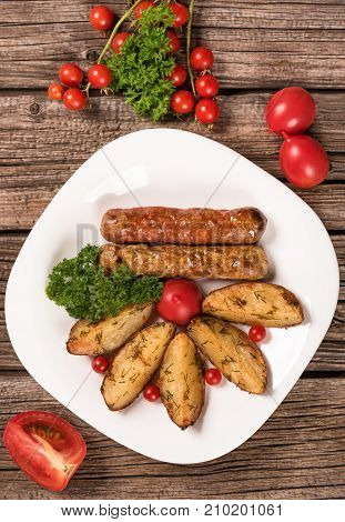 Delicious grilled wieners with fried potatoes and vegetables over wooden background