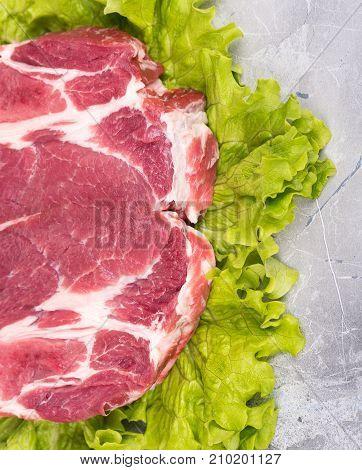 Fresh raw pork on green lettuce leaves over table-top background