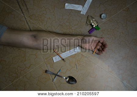 The Hand Of The Addict Is Lying On The Floor After Taking The Dose. Death Of A Drug Addict