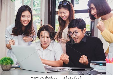 Group of young euphoric students watching exam results in a laptop in a table of an university .