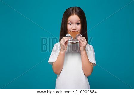 Cute Little Girl In Tee Shirt With Long Hair, With Candy Bar In Hands