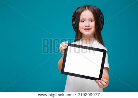 Beauty Little Girl In Tee Shirt And Earphones With Long Hair Hold Tablet