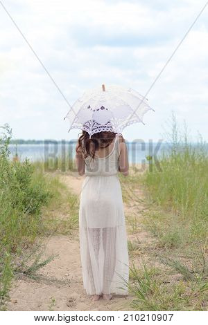 back of woman on beach path with an umbrella