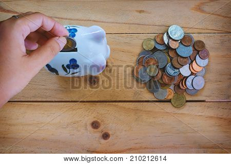 Top view of hand saving coin to piggy bank and a pile of Thai baht coins on wooden table for business and finance concept