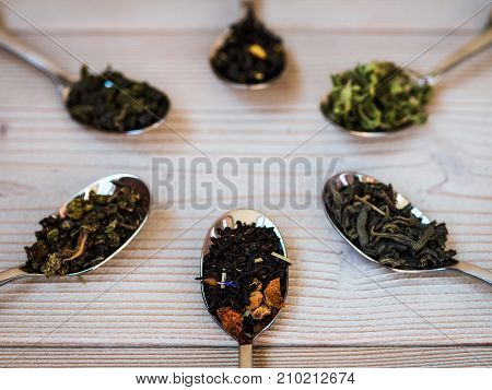 A few spoonfuls of tea on the wooden background. Shallow focus