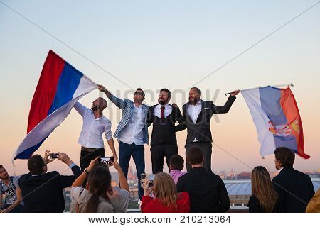Moscow, Russia - Sep 23, 2017: Tourists having fun, rejoicing and waving Serbian flags in Moscow on the Sparrow hills, on the observation deck