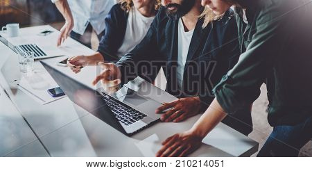Working process at office.Group of young coworkers work together modern coworking studio.Young people making conversation with partners.Horizontal Wide.Blurred background