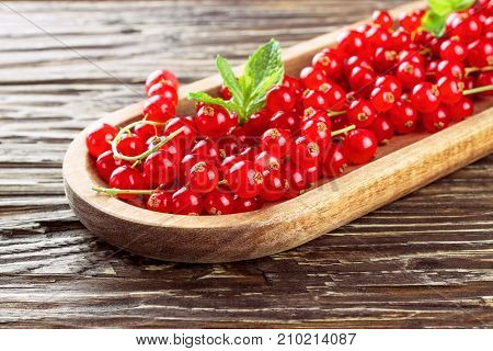 Ripe redcurrants in a wooden plate on a wooden background.