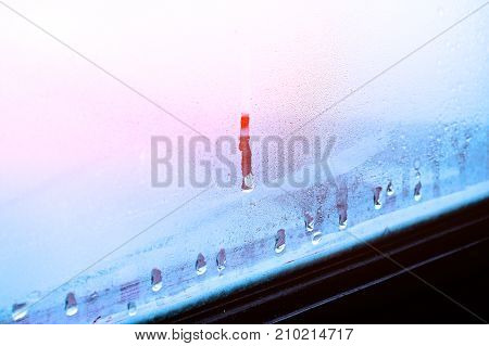 High humidity, condensing large drops of condensed water flow down the glass. Texture of water on a glass background