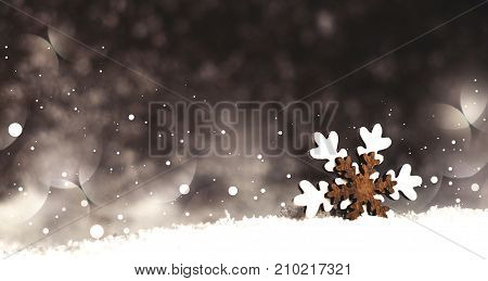 snowflake wooden toy in snow on a dark background