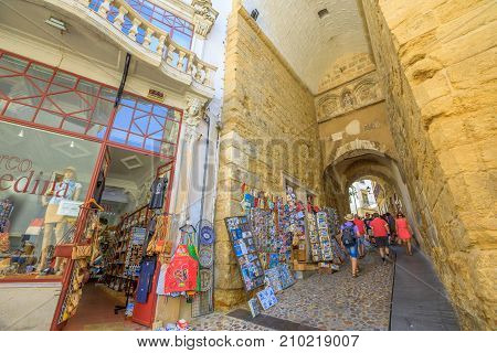 Coimbra, Portugal - August 14, 2017: tourists walking through historic gate Arch of Almedina, the iconic Archway of Almedina, famous landmark in medieval Coimbra, Central Portugal. Urban alley street.