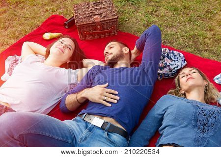 three friends having a picnic and enjoying the sun in autumn
