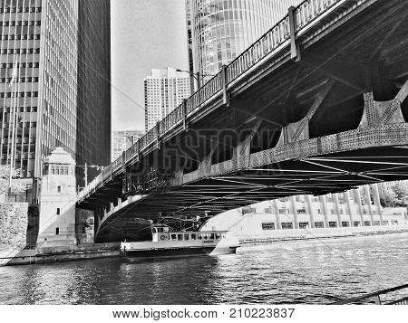 A boat crosses a bridge on the Chicago river