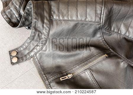 Stylish black leather jacket on the floor.
