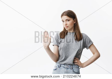 I'm not going to discuss it. Portrait of handsome confident caucasian girl with brown hair gesticulating with hand, showing she don't want to listen her boyfriend that trying explain he not cheating