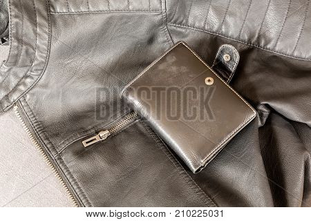 Stylish black leather jacket and a wallet on the floor.