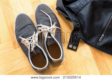 A pair of used sneakers and a leather jacket on the floor.