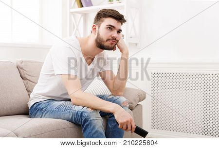 Young man watching television, using remote control to switch channels. Guy bored with what he sees on TV screen. Sitting on couch in living room at home, copy space