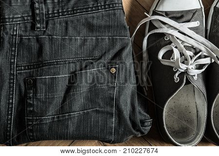 Grey sneakers and jeans on the floor.