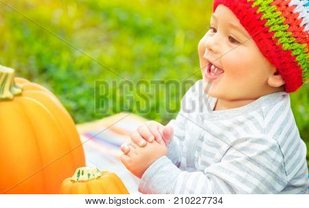 Closeup portrait of a nice cheerful baby boy laughing and enjoying time spending outdoors, sitting near two pumpkins, traditional symbol of Thanksgiving day