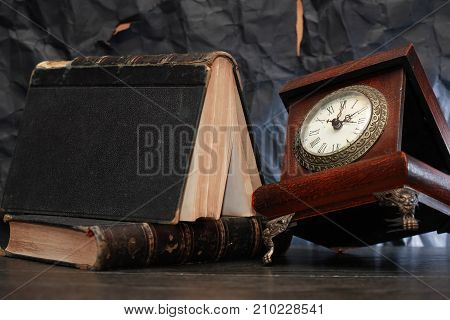 Old wooden clock near book on nice gray background