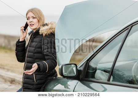 Accident and breakdowns with auto concept. Broken down car blonde woman having problem calling to somebody for help.