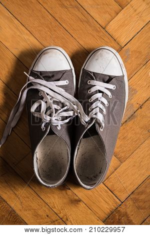 A pair of used sneakers on the floor.
