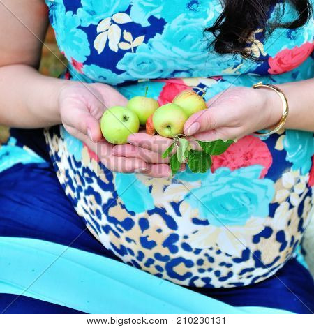 Image of pregnant woman touching her belly with hands
