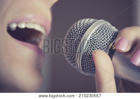 A woman sings into a microphone at a recording studio her mouth close up