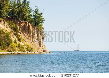 Landscape Of Cliff Near Sea And Ship On Water
