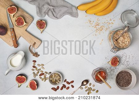 Ingredients for breakfast: oatmeal milk figs bananas chia seeds honey pumpkin seeds. view from above