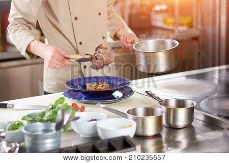 Chef hands holding cooked lamb shank. Male chef putting on lamb shank into plate with garnishing. Preparation of tasty dish at european restaurant kitchen.