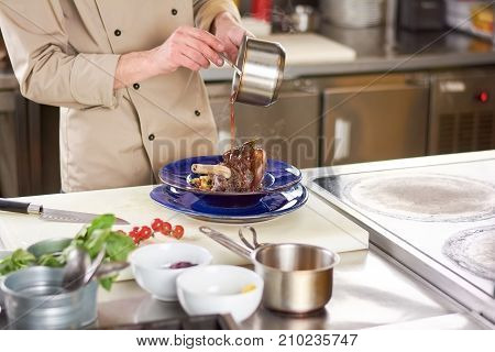 Chef pouring sauce on lamb shank. Male chef pouring with sauce fresh cooked beef shanks at european restaurant.