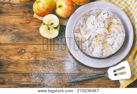 homemade apple pie on a plate sprinkled with sugar powder napkin fruit on a wooden table rustic style top view