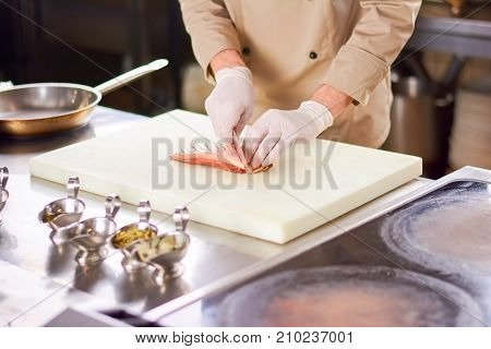 Male chef dicing meat of poultry. Chef at work cutting meat on white board. Preparing duck fillet.