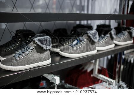Shoes - grey sneakers on the shelf in the store.