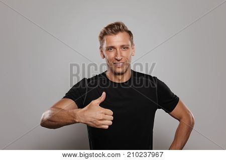 Handsome muscular man in black sportive shirt smiling at camera holding thumb up on gray.