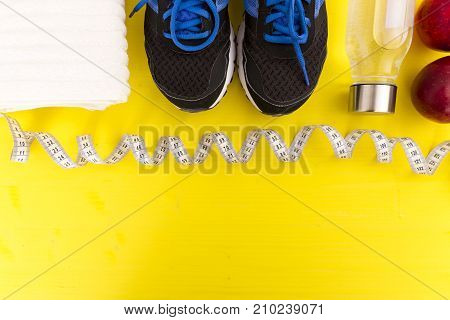 Fitness equipment. Healthy food. Sneakers waterapple measuring tape on yellow wooden background