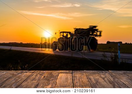 Empty Rustic Wood Table Top With Tractor Silhuette At Sunset Background. Can Montage Or Display Your