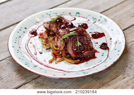 Chopped meat in sweet red sauce. Juicy beef meat on plate, old wooden background. Delicious european cuisine.